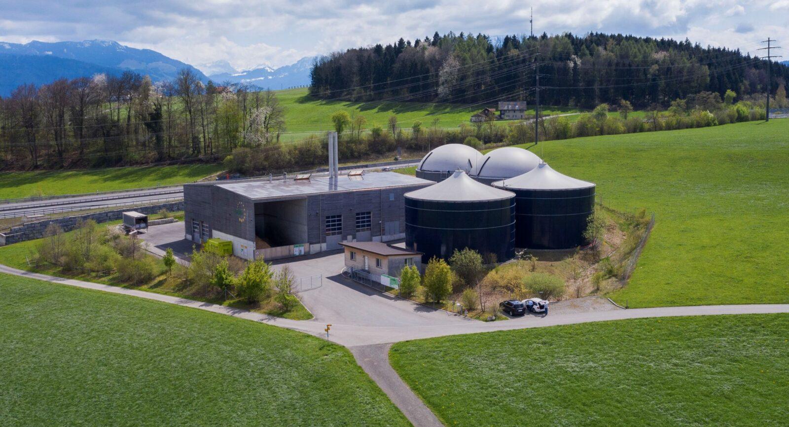 Flugaufnahme auf die Biomasse-Heizkraftwerk mit Werkgebäude (li.), 2 Fermenter mit Gashauben (re. i. Hintergr.), 2 Güllenlager (re. i. Vordergrund)